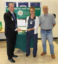 Laura Reynolds with CEO Jeremy Clark receiving DAISY award